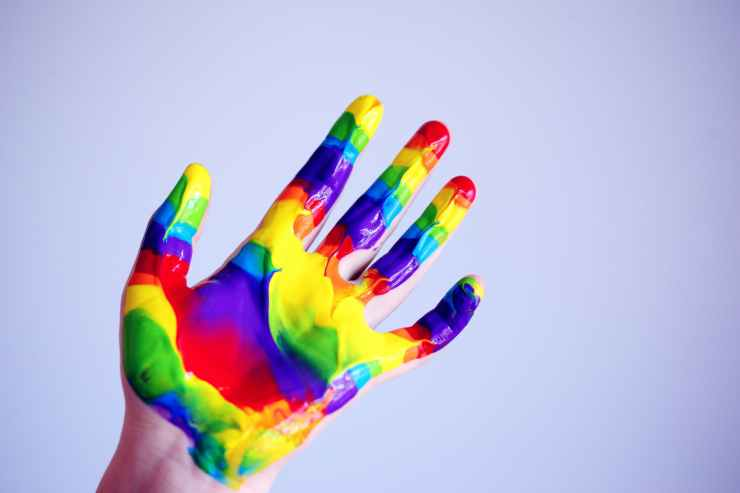person s hand with paints